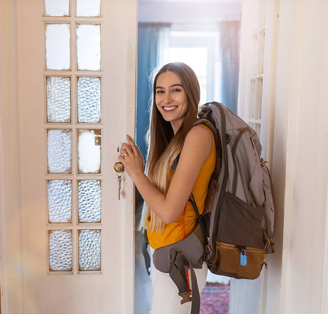 Photo of a young woman with a backpack in a doorway.