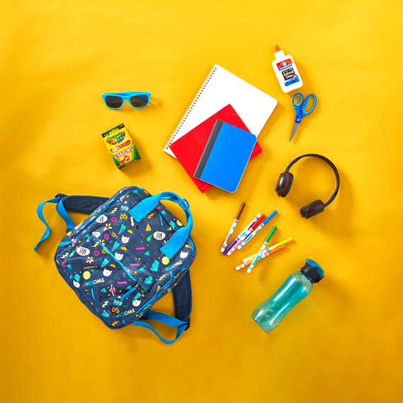 Photo of a backpack with school supplies laying next to it.
